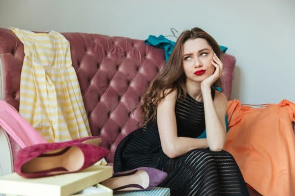 Woman not looking confident sitting on comfortable couch with clothes