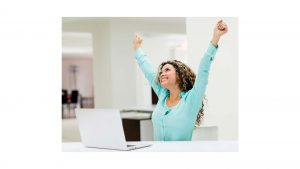 Woman at computer with arms in air looking happy and excited