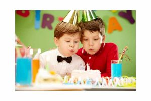 two little boys blowing out birthday candles